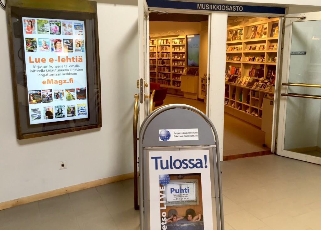 Metso LIVE -tapahtumat ovat esillä kirjastossa selkeästi. Ovelle sijoitetun julisteständin lisäksi musiikkiosastolla on kaksi info-TV:tä, toinen sisäänkäynnillä, toinen osastolla.